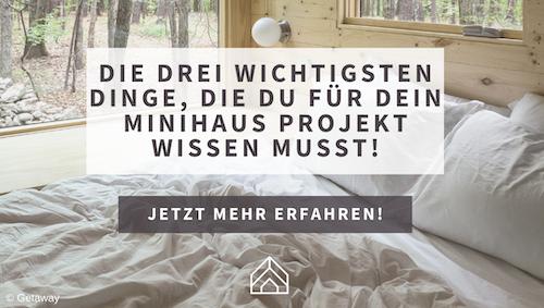 Das Bild zeigt ein Minihaus von Innen. Man sieht ein Schlafzimmer mit einem großen Fenster nach draußen