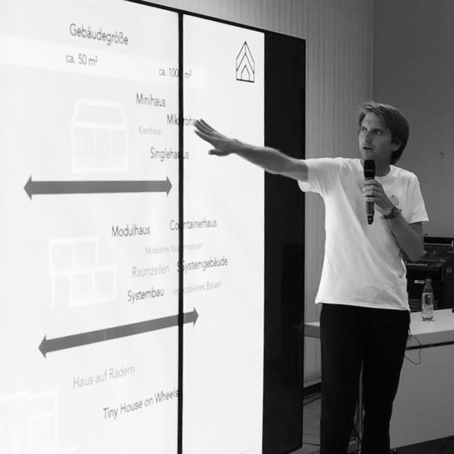 Das Bild zeigt den Tiny House Experten Christian Brecht bei einem Vortrag. Zu sehen ist der Referent und eine Powerpoint Präsentation über Tiny House Typen.