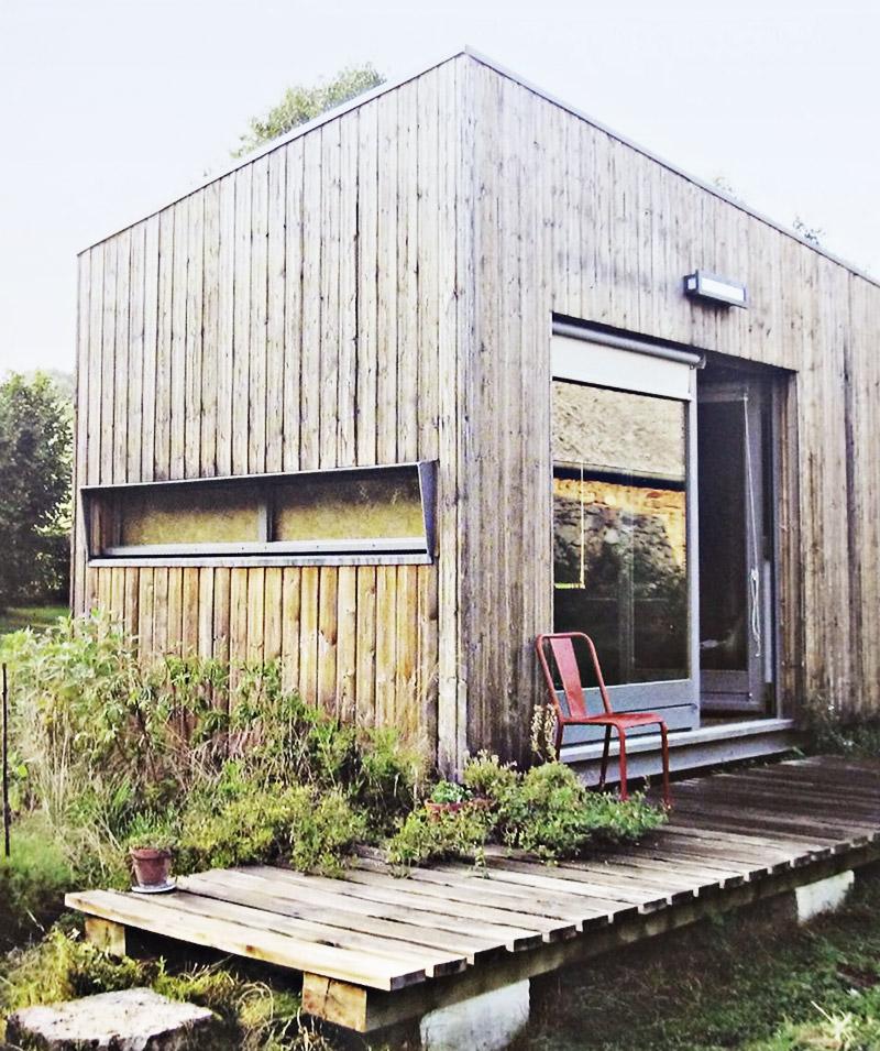 Das Bild zeigt ein Minihaus mit Holzfassade. Vor der dem Minihaus ist ein Holzterrasse.