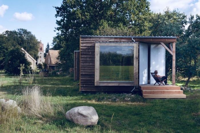 Das Bild zeigt ein Minihaus in einem großen Garten. Im  Hintergrund des Minihauses sind Bäume erkennbar.  Eine Frau sitzt vor dem Minihaus in einem Sessel.