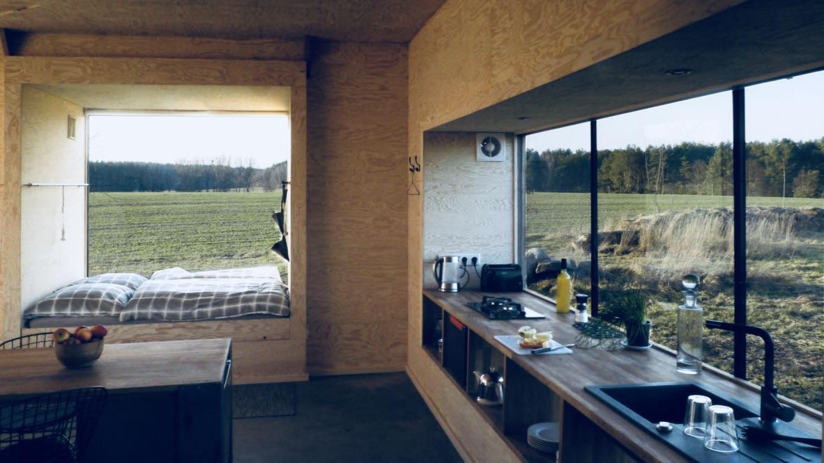 Das Bild zeigt ein Minihaus von innen. Im Minihaus sieht man eine Küche mit einem großen Fenster und einem Schlafplatz.