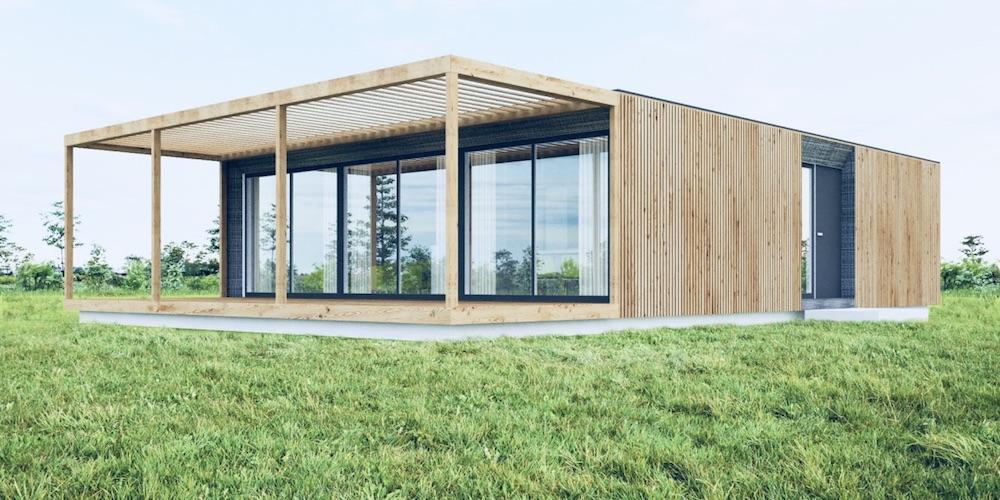 Das Bild zeigt ein Modulhaus auf einer grünen Wiese.  Das Modulhaus hat eine Außenfassade aus Holz mit einer großen Fensterfront