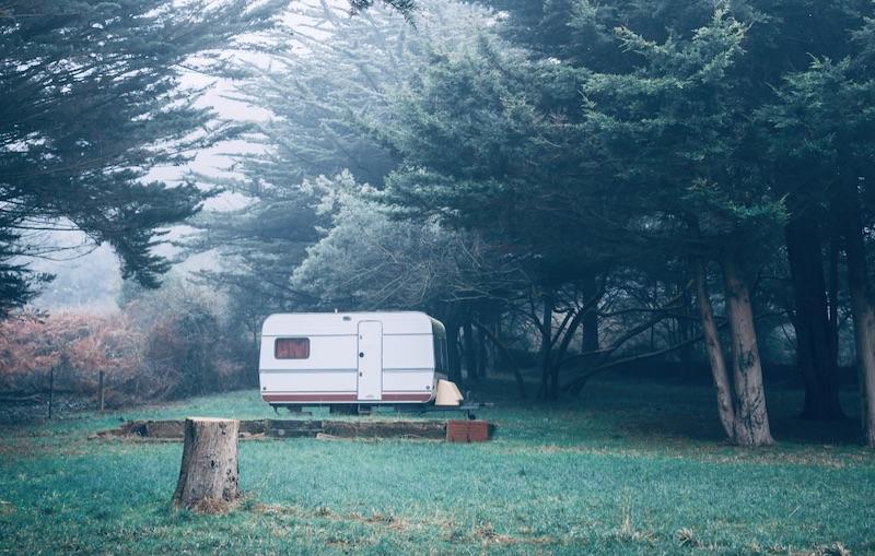 Das Bild zeigt die Nutzung als Wohnwagen auf einem schönen Grundstück mit Bäumen - wofür keine Baugenehmigung benötigt wird
