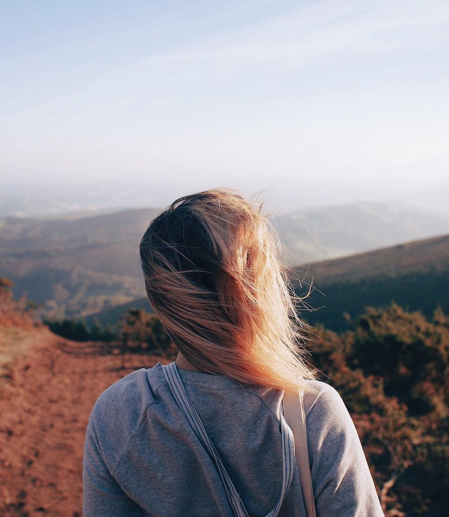 Das Bild zeigt eine junge Frau mit blonden Haaren die in die Landschaft blickt und vermittelt die Freiheit die ein Tiny House ermöglicht