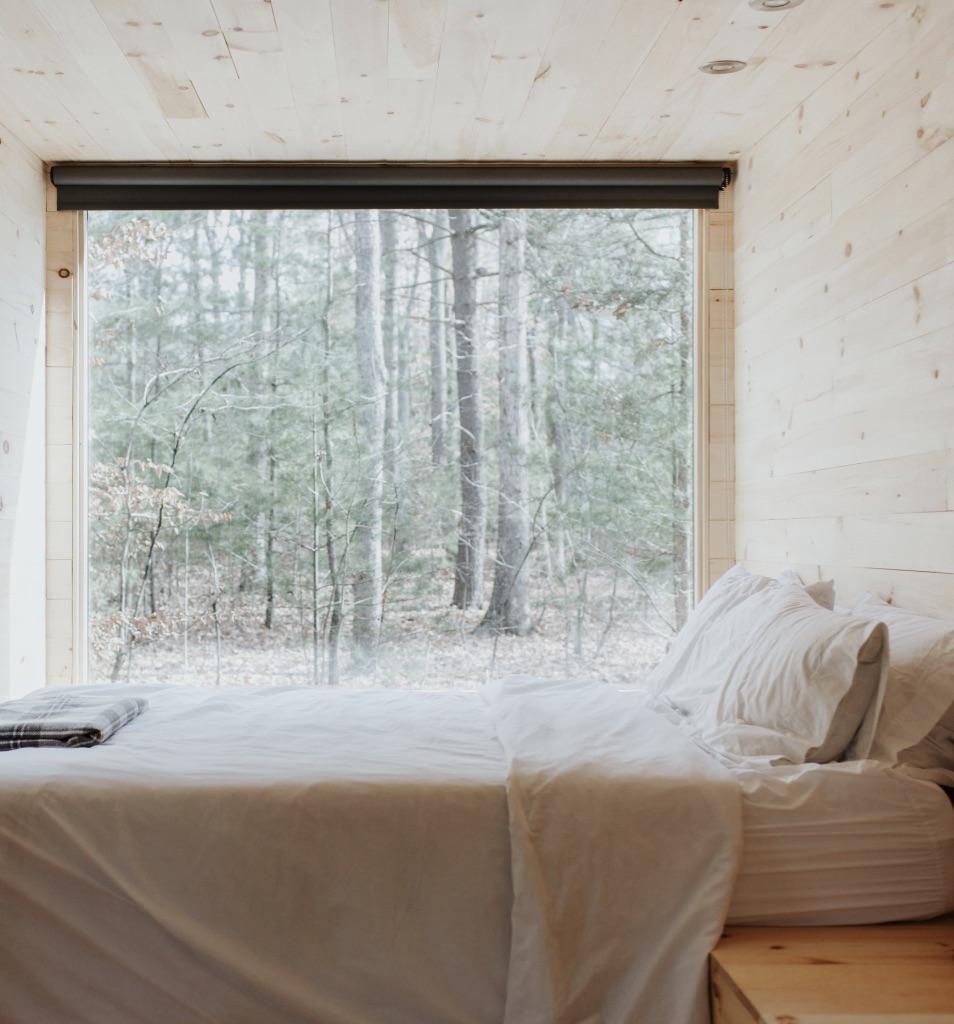 Das Bild zeigt ein Tiny House von Innen. Man sieht ein Schlafzimmer mit einem großen Fenster.