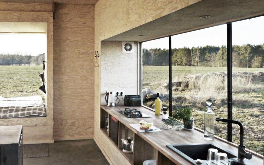 Das Bild zeigt ein Tiny House von innen. Im Tiny House sieht man eine Küche mit einem großen Fenster und einem Schlafplatz.