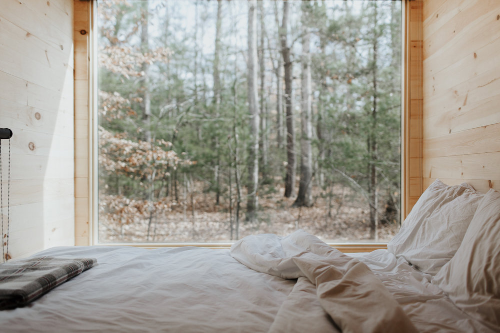 Das Bild zeigt ein Haus auf Rädern von innen mit Blick nach draußen. Zu sehen ist ein Wald