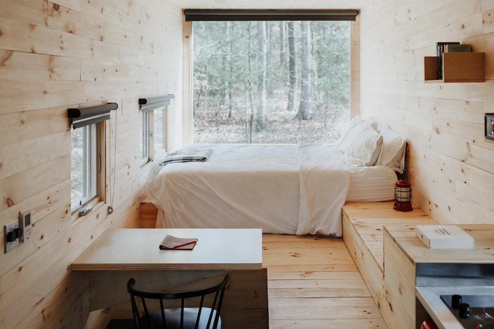 Das Bild zeigt ein Haus auf Rädern von innen. Zu sehen ist ein Wohnbereich mit Küchentisch und Bett