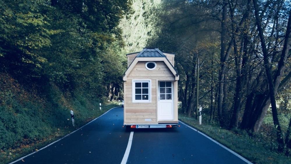 Bild zeigt den Transport eines Hauses auf Rädern. Zu sehen ist eine Straße und ein Wald. Das Haus auf Rädern wird auf einem Trailer von einem PKW gezogen