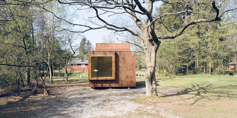 Das zeigt ein Minihaus auf einem schönen Grundstück. Vordergrund ist ein Baum zu sehen.