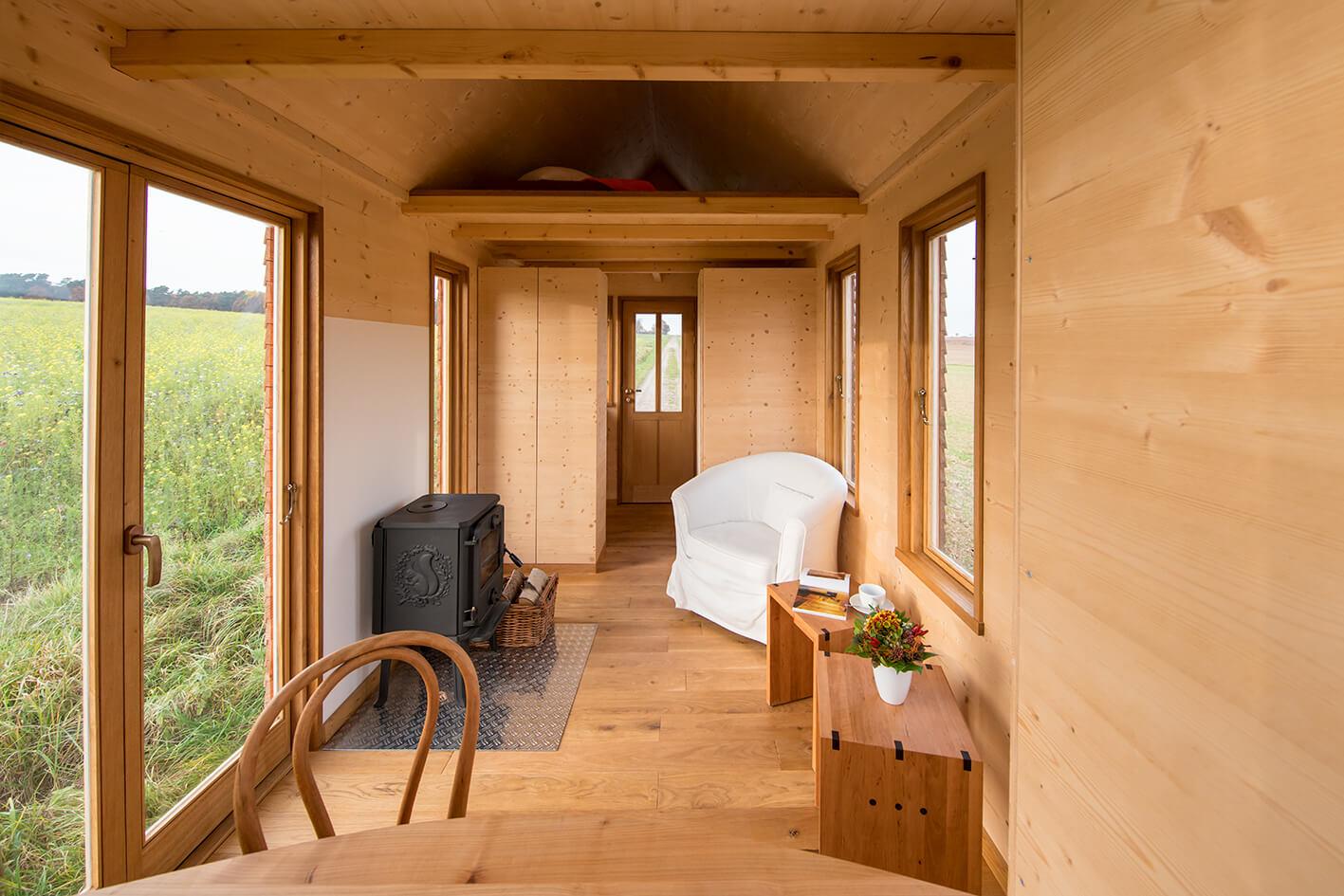 Das Bild zeigt ein Tiny House von innen. Zu sehen ist ein Tiny House on Wheels mit einem Wohnbereich und Schlafbereich.