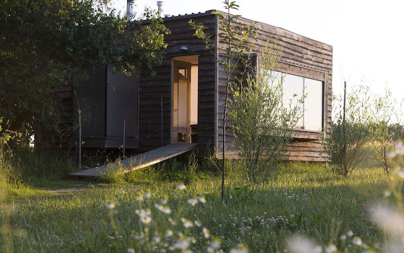 Das Bild zeigt ein gut gedämmtes kleines Haus auf einer grünen Wiese