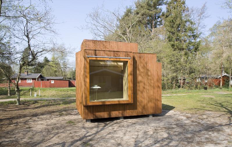 Das Bild zeigt ein Tiny Haus auf einem Grundstück. Zu sehen ist das großes Fenster mit einer Holzfassade