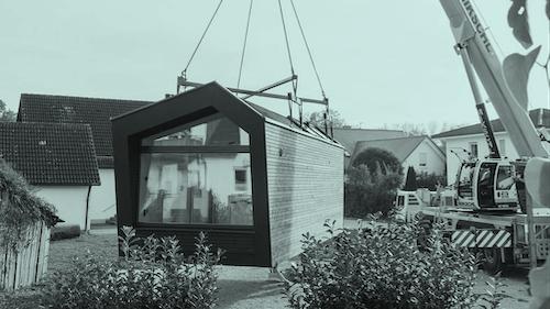 Das Bild zeigt ein Tiny House, dass auf ein Grundstück mit einem Schwerlastkran gehoben wird